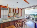 Kitchen bar with open pocket lanai doors for seamless outdoor living experience