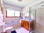 large bathrooom area with full bath, toilet, separate shower and handbasin