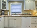 The kitchen features granite countertops and white cabinetry.
