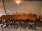 Planta principal. Salón en dos alturas con decoración rústica y mesa grande