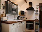 A beautifully fitted kitchen includes a dishwasher, hob, oven, fridge, microwave, kettle & toaster.