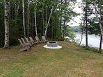 Adirondack chairs surrounding fire pit at water's edge