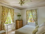 Guest bedroom with dual aspect windows onto lush tropical gardens and the bay
