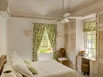 Master bedroom with dual aspect windows onto lush tropical gardens