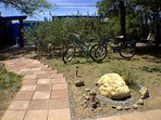 Found boulder moved to accent the existing ornamental grass, along with found rock/metal ant. Bikes.