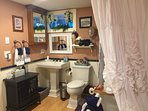 Spacious beautiful bathroom with antique clawfoot tub and an electric fireplace for added ambience