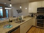 Kitchen professionally designed with granite counters and double over range
