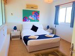 Upper floor spacious master bedroom with king size bed and views of sea and mountains.