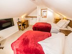 The upstairs bedroom has 2 single beds, a large smart TV and oak furniture