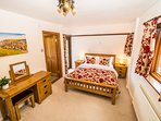 The master bedroom has a king size bed and oak furniture