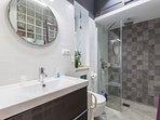 Baño moderno y funcional con mampara de cristal y suelo antideslizante