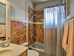 There's a shower/tub combo in this full bathroom.