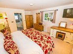 The master bedroom has a super king size bed with large smart TV. Beautiful Oak furniture