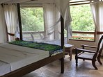 Master bedroom with view of ocean and forest