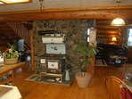 Antique wood fired stove as center piece on 2 sided 2 storey rock fireplace