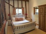 Large bedroom with king-sized bed, carpeted with high ceilings and period features i.e.wooden beams