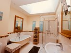 Yellow en suite shower and bathroom. All bathrooms have shaver sockets & mirrors