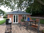 Sunny patio area with table & chairs & bbq overlooking acres of green fields with resident cows