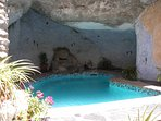 refreshing pool with integrated jacuzzi, set into a cave