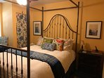 Bedroom features queen brass bed, luxurious down bedding, TV, dresser, desk, fridge, ensuite coffee