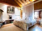Habitación con cama Queen y horno de piedra tradicional recorvertido a chimenea.Baño completo .