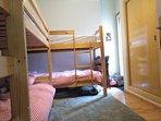 Luminoso y amplio dormitorio con 4 camas de 90 cm, armario empotrado y luz natural.