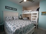 Queen and 2 twin bunks with whitewashed shiplap trim. Fun linens and a bear.