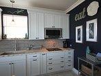 SurfSide blue cabinets, leathered granite, beachy backsplash, and whitewashed.