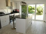Kitchen with American fridge freezer, range cooker, granite worktops & bifold doors to garden.