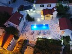 Peacful summer evening aerial view of Fuga and its spacious courtyard featuring it lovely pool
