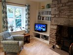 Cosy lounge with feature stone fireplace and warming fire