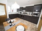 A modern fully equipped kitchen & dining area.
