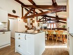 Open plan kitchen and dining areas beneath the original beams