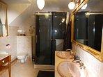 Badkamer met regendouche, dubbele wastafel en toilet.