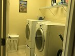 Separate laundry room with full size front load washer and dryer