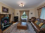 Sitting room with open fire, sky tv and views over landscaped gardens