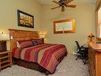Master bedroom with king bed,  desk/chair, dresser, remote fan, large closet