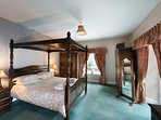 Master bedroom with king size four poster bed, en suite and balcony overlooking gardens.
