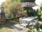 Extérieur privatif l'Oustal avec transat, salon de jardin, parasol et barbecue en dur