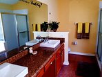 En suite bathroom with twin basins and walk in shower, garden tub and toilet.