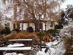 Snow covers the snug house and garden.