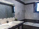 Bathroom with bath tub and double washbasin