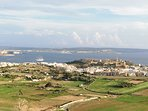 Ghajnsielem with Fort Chambray (right). Behind the Mediterranean with Comino (left) and Malta.