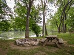Large campfire pit and picnic table by river