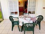 Salon jardin  table installée  sur la terrasse  donnant sur le jardin  accès piscine
