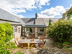 The rear of the house with new conservatory and sheltered courtyard with outdoor table and chairs.