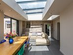 Light filled conservatory dining room with underfloor heating and a very comfy sofa for relaxing.