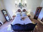 The romantic bedroom with original antique bed and chandelier.