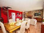 Dining and living room, fully equipped kitchen, TV, fire place and exit to terrace