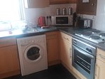 Linnhe kitchen with washer/dryer, kettle, toaster, microwave, oven & hob, and coffee maker
